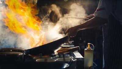 Ein kokk står ved ein komfyr og rører i ein wok med store flammar. Foto.