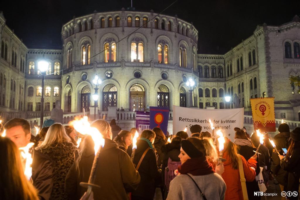 Mennesker med brennende fakler foran Stortinget. Foto.
