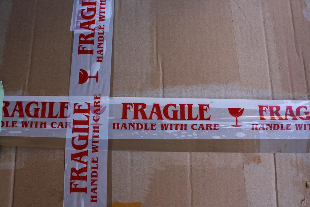 Hvit tape med rød skrift: fragile og symbol for glass.foto.
