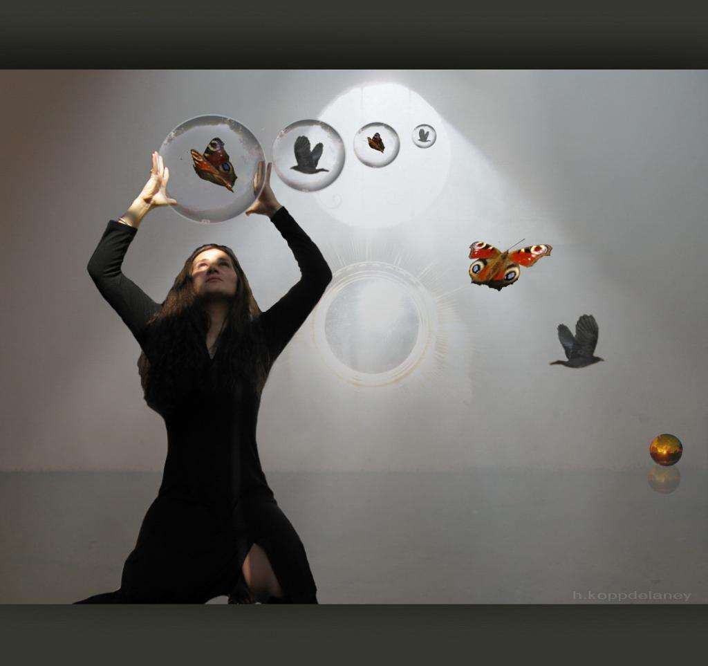 Woman catching a bubble with a butterfly inside. Photo.