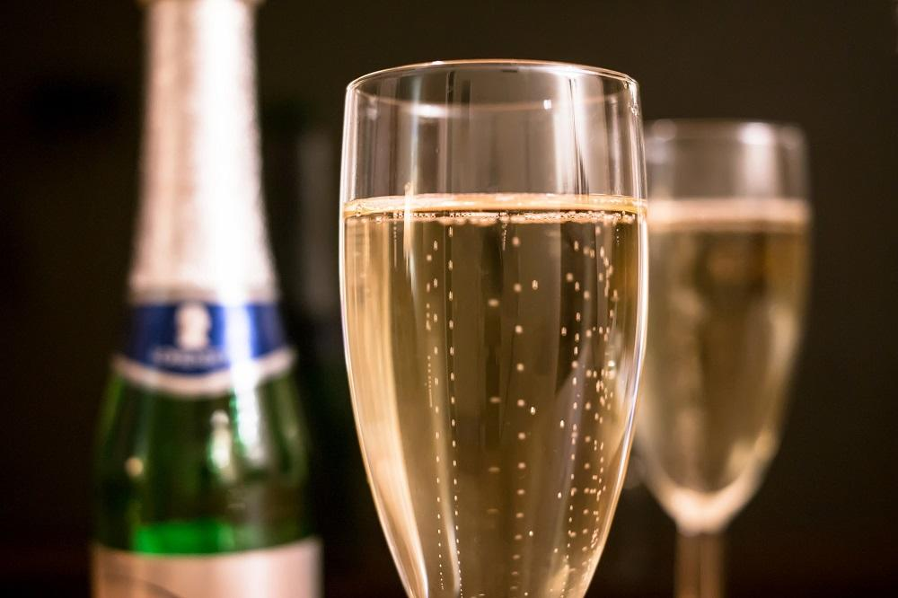 Glass med mussererende vin. Foto.