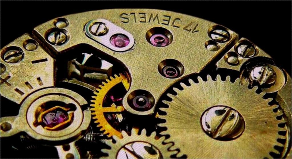 Nærbilde av tannhjula i urverket på et armbåndsur. Metallet er til dels gullfarga, til dels sølvfarga.Foto.