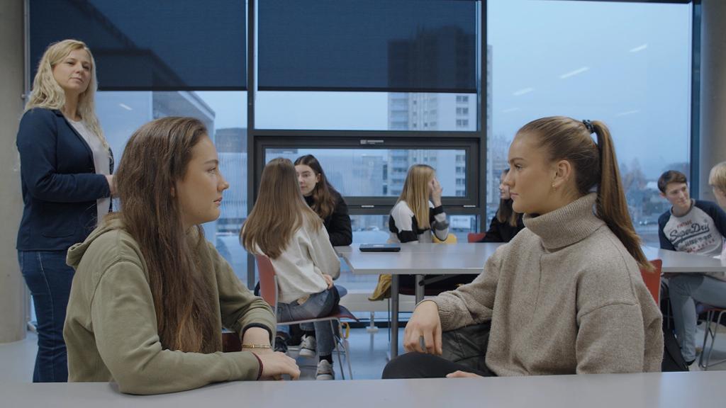 Elever som utfører kreativitetsøvelsen Mesteren. To og to sitter ved samme pult og ser på hverandre. Læreren observerer elevene. Foto.