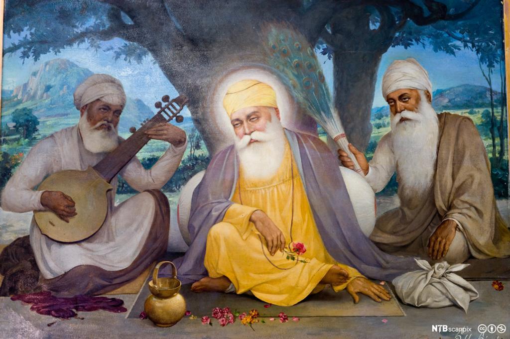 Mann i gul kjortel med turban sitter under et tre omgitt av to menn med hvit tyurban. Den ene spiller et instrument. Maleri.