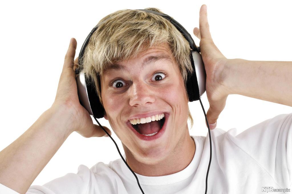 Gutt som lytter på høy musikk gjennom øretelefoner. Foto.