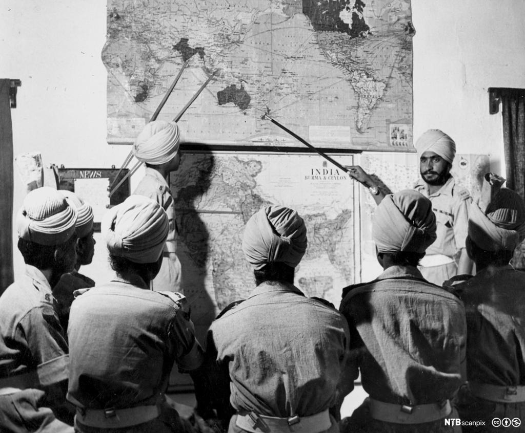 Menn med turban peker på land på et verdenskart. Fotografi.