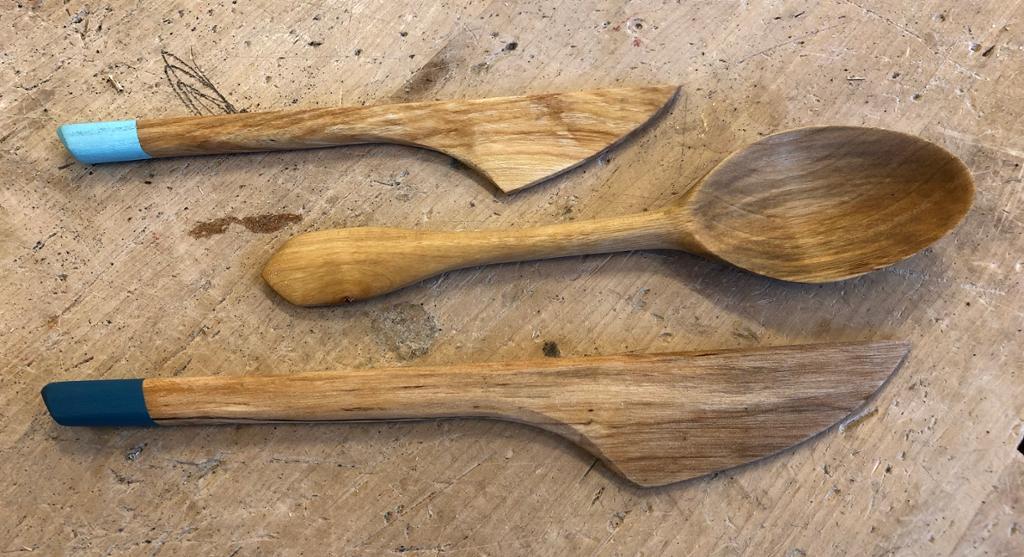 To smørkniver og ei skei utformet i tre. Foto.