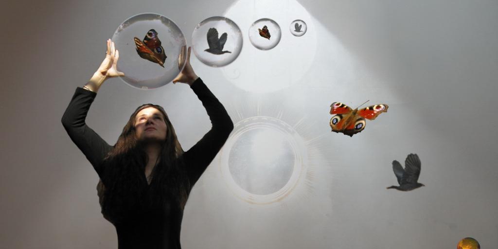 Dame holder kule med sommerfugl inni. Foto.