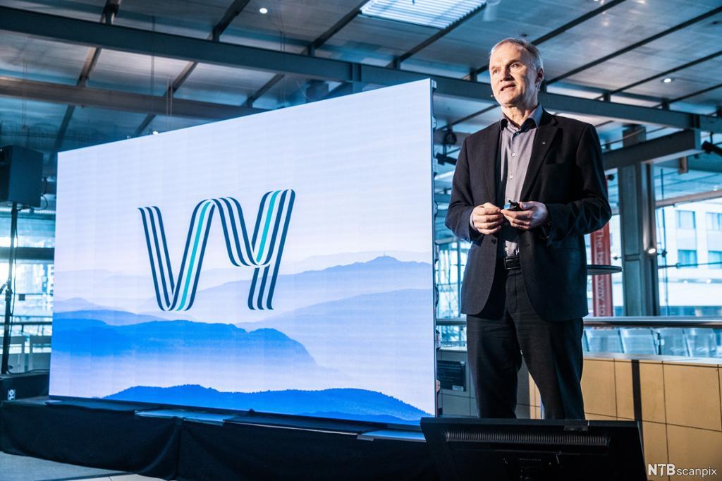 Mann ved siden av tavle med logoen til VY. Foto.