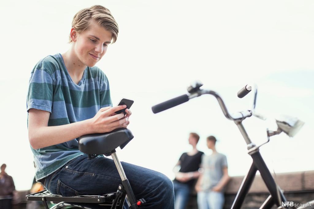 Gutt sitter på sykkel og tekster. Foto.
