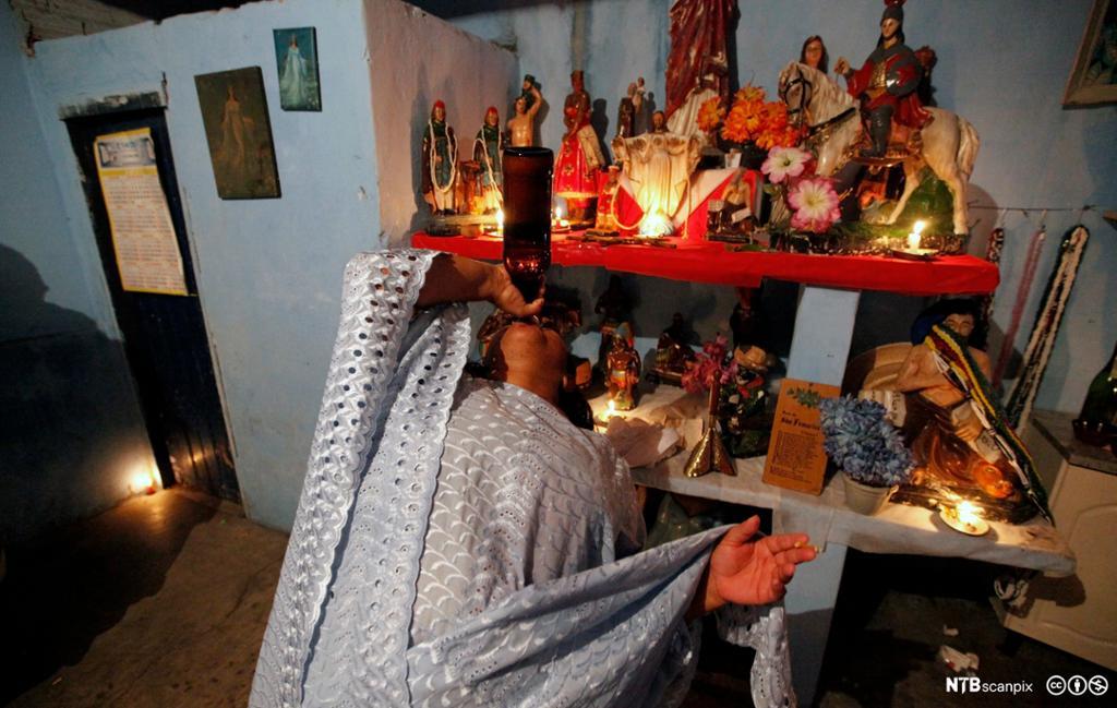 Kvinne drikker av en flaske foran et alterbord fullt av ulike figurer. Foto.