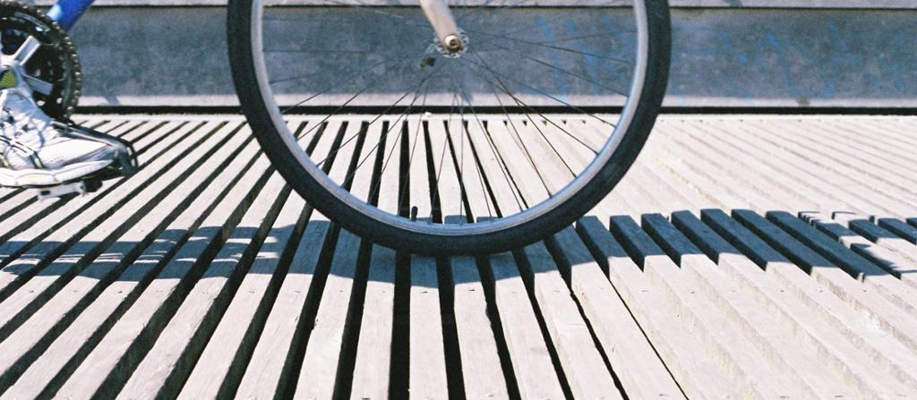 Syklist på et gulv av smale bjelker med spalter mellom. Foto.