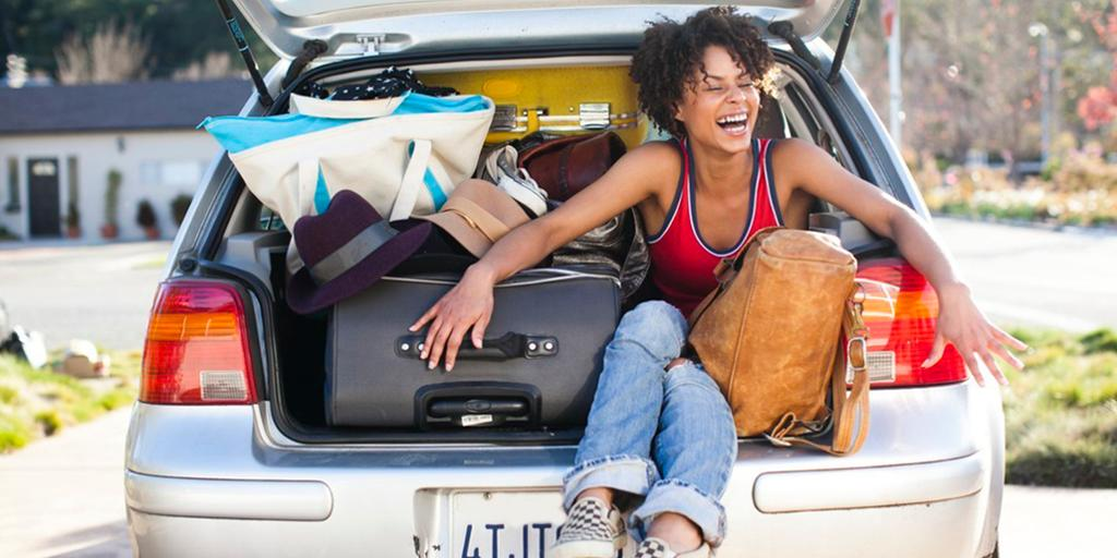 Jente sitter i bagasjerommet sammen med vesker og kofferter. Foto.