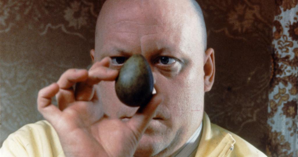 Mann i gul skjorte ser på et grønt egg. Bilde fra filmen Eggs. Foto.