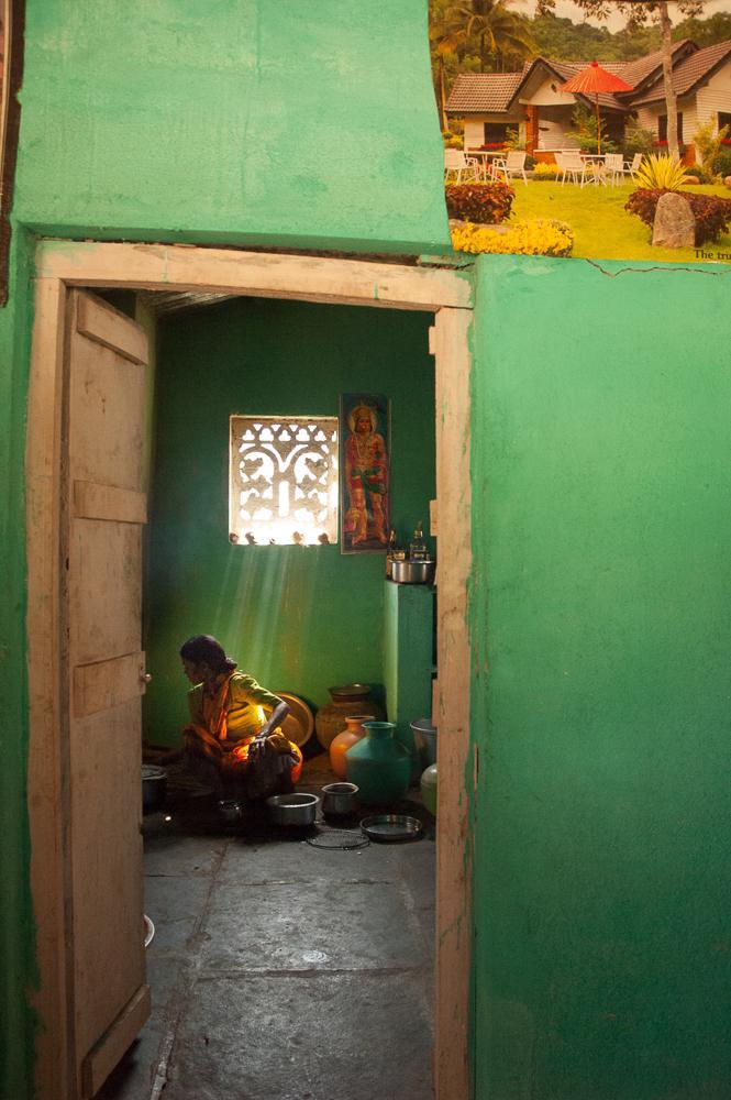 Vi ser en kvinne gjennom døra inn til et annet rom. Fotografi.