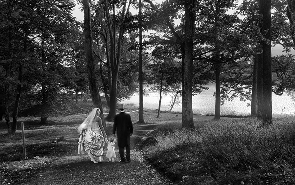 Brudepar i skogen. Paret er plassert i venstre halvdel av bildet. Fotografi.
