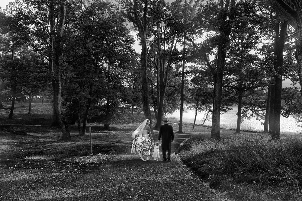 Brudepar i skogen. Paret er plassert midt i bildet. Fotografi.