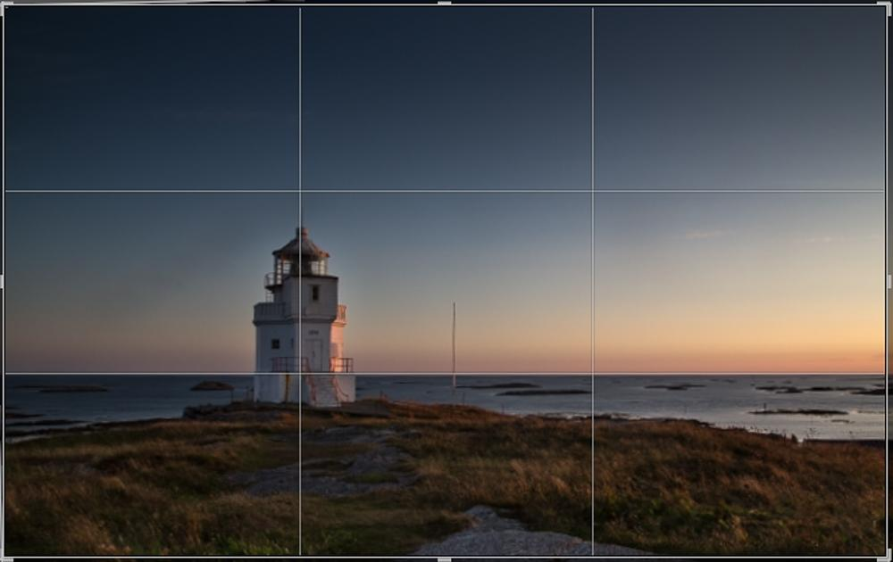 Fyrlykt med hav og horisont. Bildeflaten er delt i tre vertikalt og horisontalt. Fotografi.