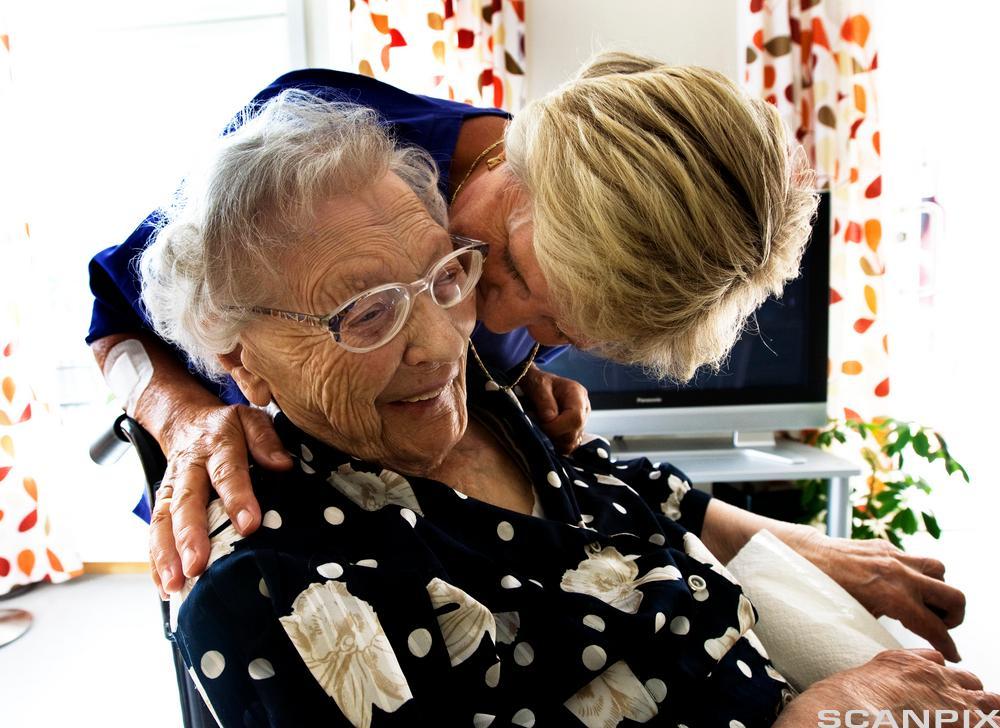 Omsorgsarbeider står bak ei eldre dame som sitter i en stol. Omsorgsarbeideren har hendene på skuldrene til dama og bøyer seg mot øret hennes for å si noe. Foto. Foto.