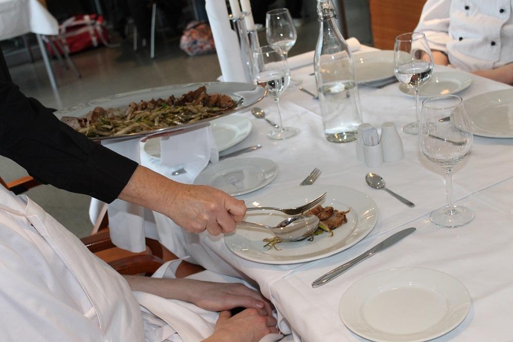 Servitør legger mat på gjestens tallerken. Foto.