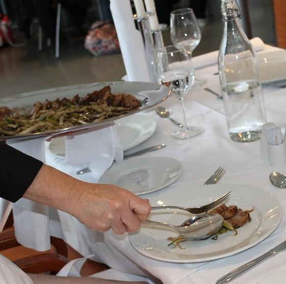 Servitør utfører engelsk servering. Foto.