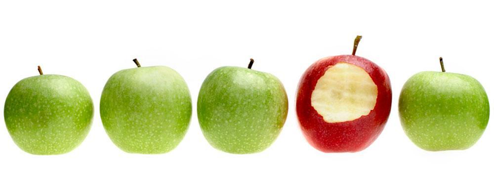 Fire grønne og et rødt eple som er spist av. Foto.