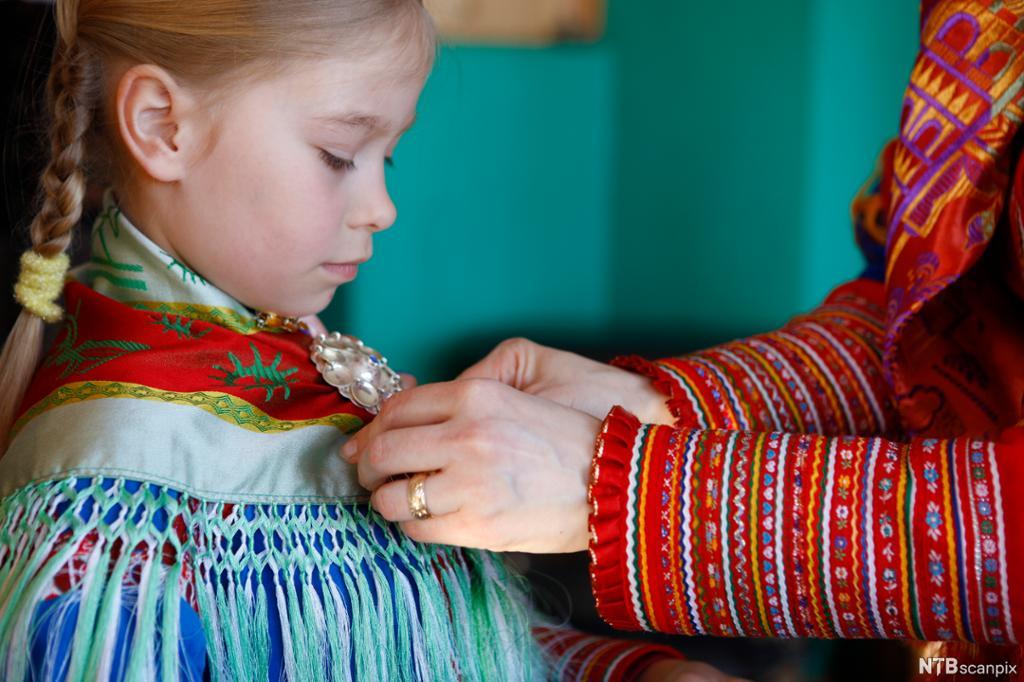 Ei jente og ei dame kledd i samiske klær. Dama hjelper jenta med sjalet. Foto.