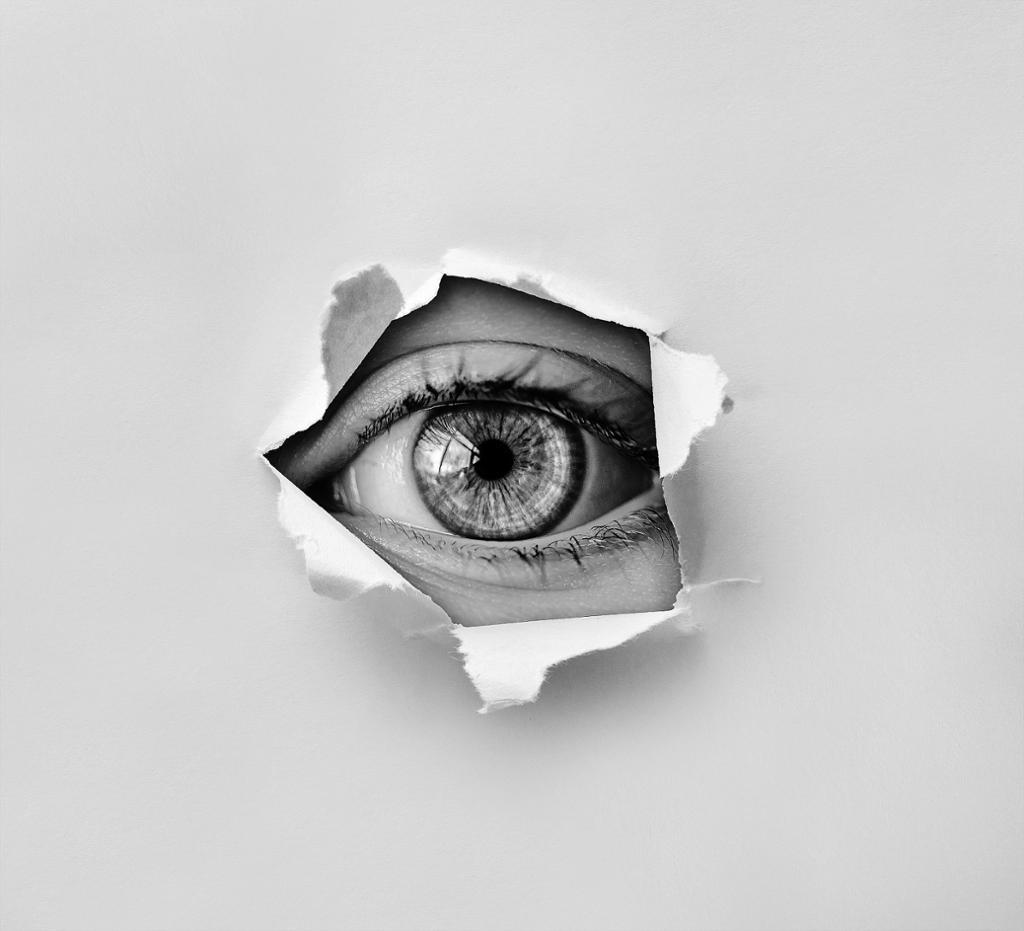 Øye ser gjennom et hull i et papir. Foto.