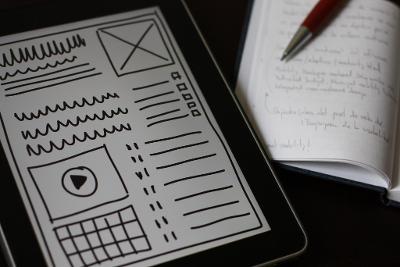 Nettbrett med skisse av nettside eller app med streker, ruter, punkter og lister som viser hvor ulike typer innhold er tenkt plassert. Foto.