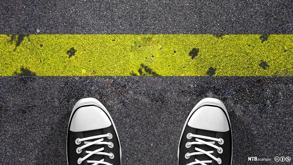 En person med  joggesko står foran en gul strek. Grense. Foto