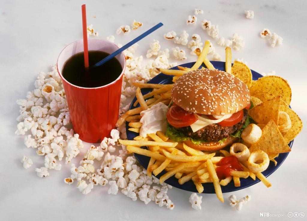 Pappbeger med brus og tallerken med hamburger og chips. foto.