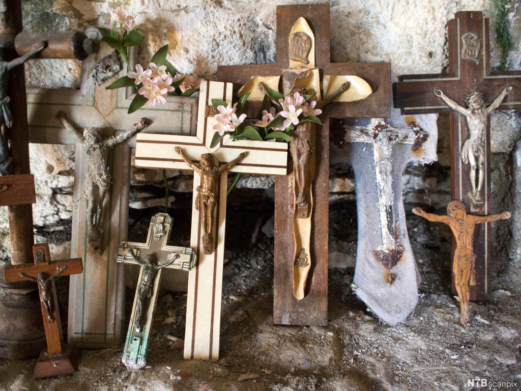 Syv ulike figurer av Jesus på korset stilt opp mot en vegg. Pyntet med blomster. Foto.