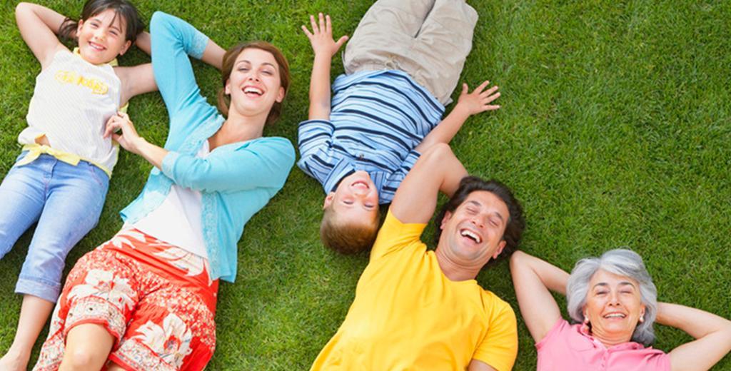 Familie på fem, tre generasjoner, liggende på en gressplen. Foto.