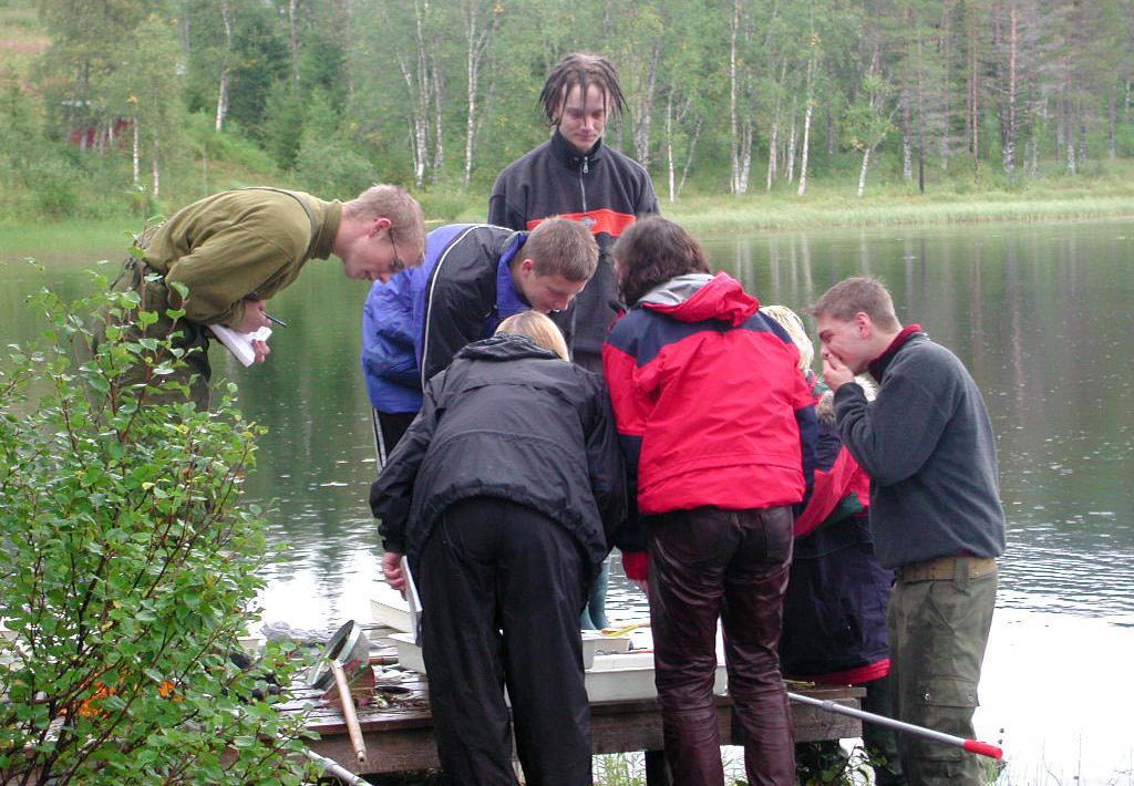 En gruppe ungdommer står bøyd over fangst fra ferskvann. Foto.