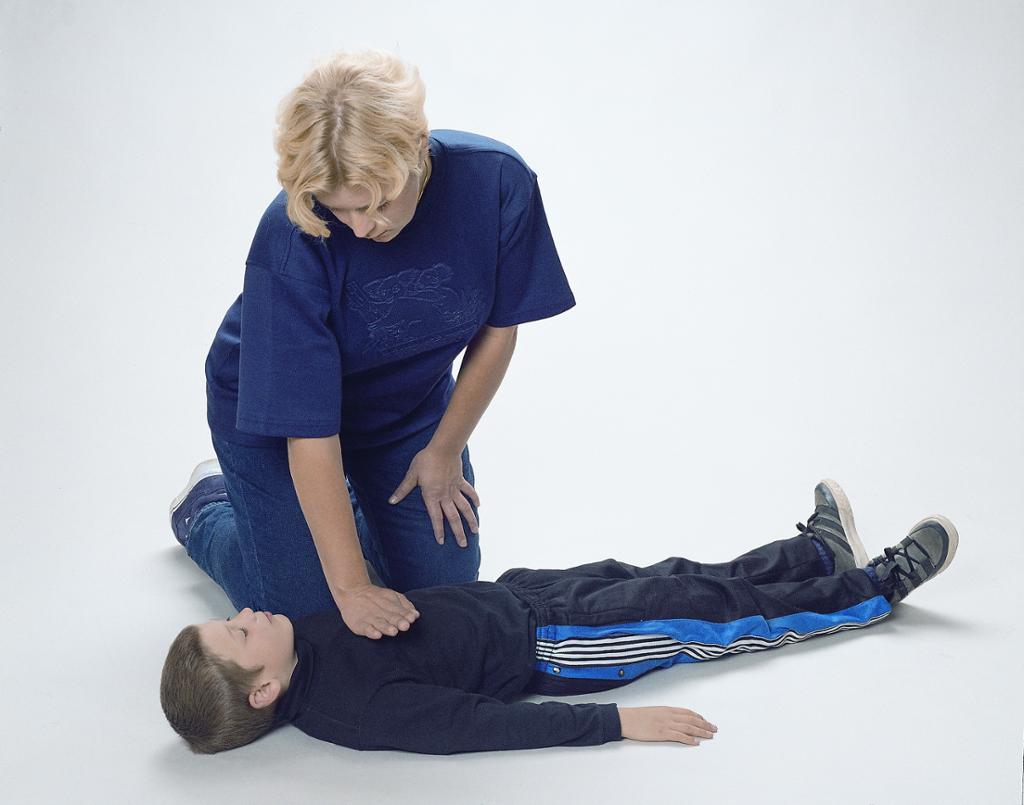 Dame demonstrerer hjertekompressjon på et barn. foto.