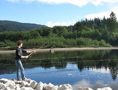 Gutt med fiskestang ved Namsenvassdraget. Foto.