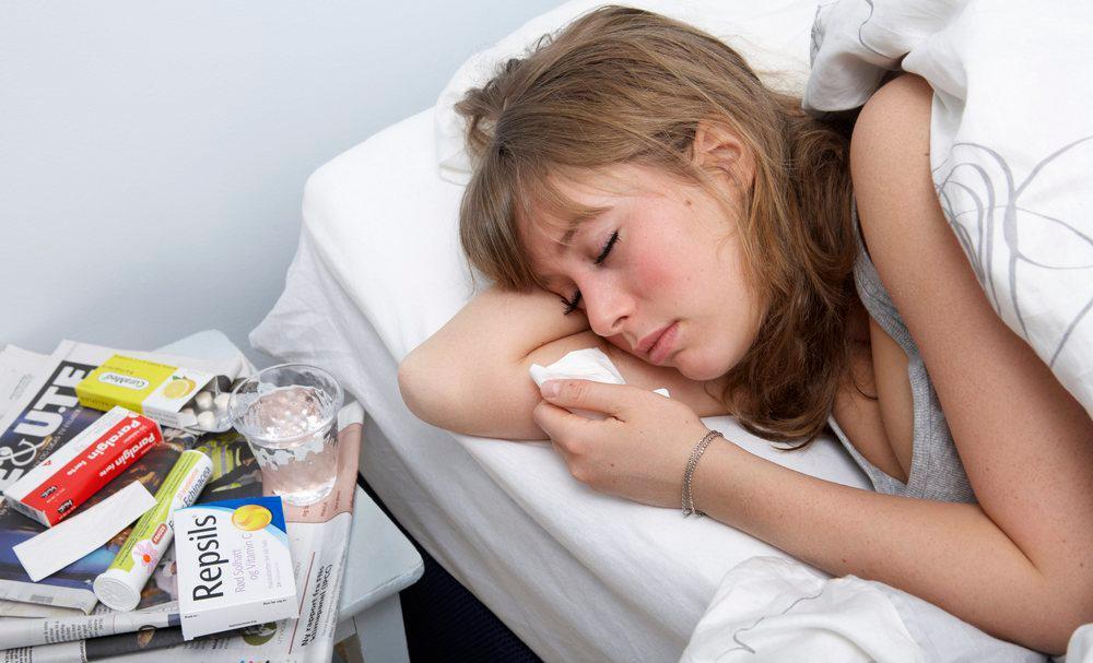 Syk jente ligger i seng og har medisiner på nattbordet. Foto.
