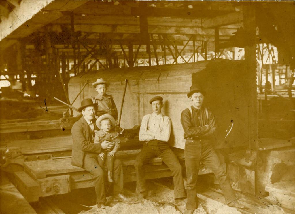 Tre voksne og to barn i et gammelt sagbruk. Fotografi.
