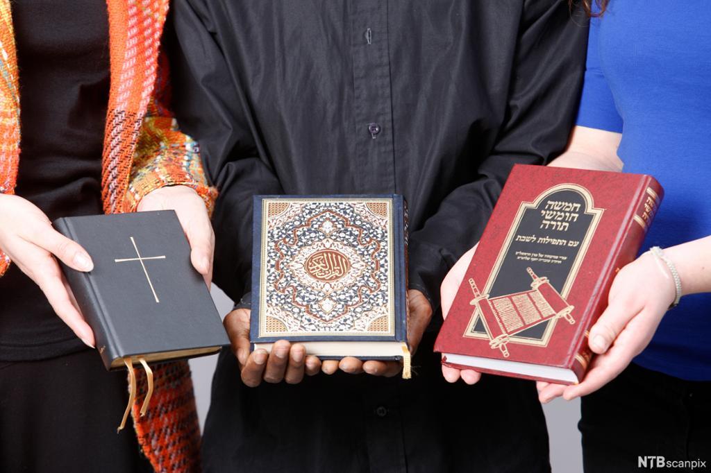 Tre personer holder frem hver sin bok. Boka til venstre har et kors på omslaget. Boka i midten har arabisk skrift og utsmykning. Boka til høyre har hebraisk skrift med bilde av en skriftrull. Foto.