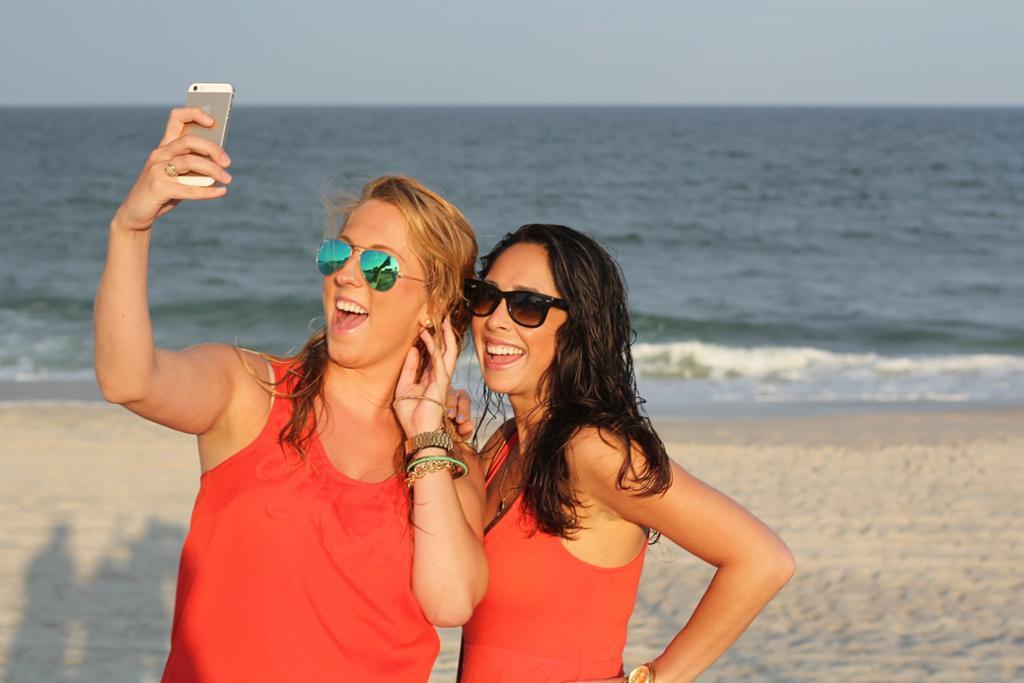 To jenter på ei strand som tar selfie sammen. Foto.