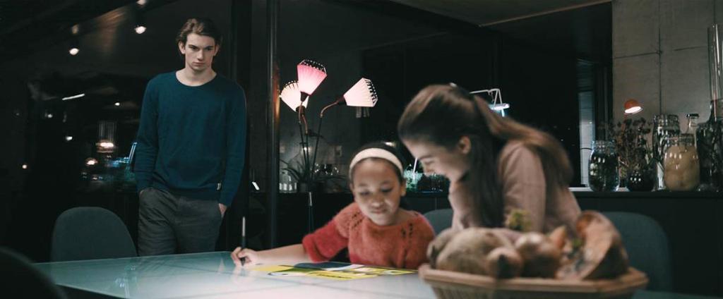 Mor, barn og tenåring ved et bord. Foto.