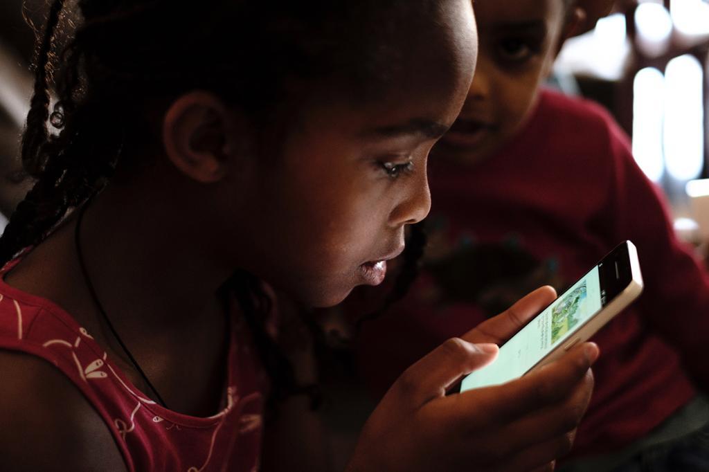 Afrikansk barn les på mobil. Foto.