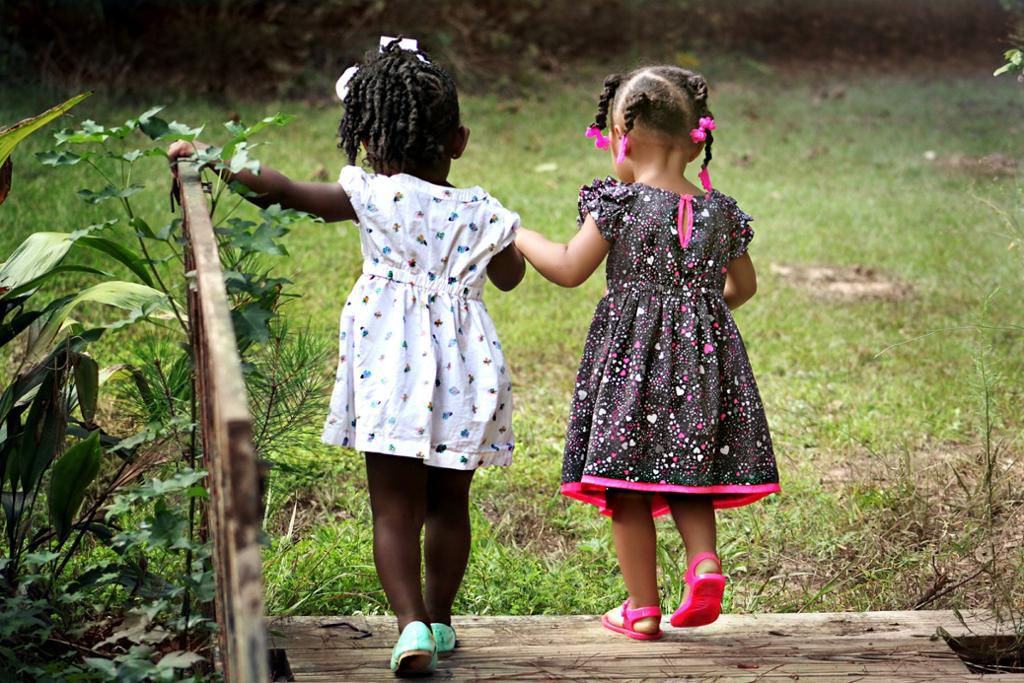 To jenter med sommerkjole leier hender. Foto.