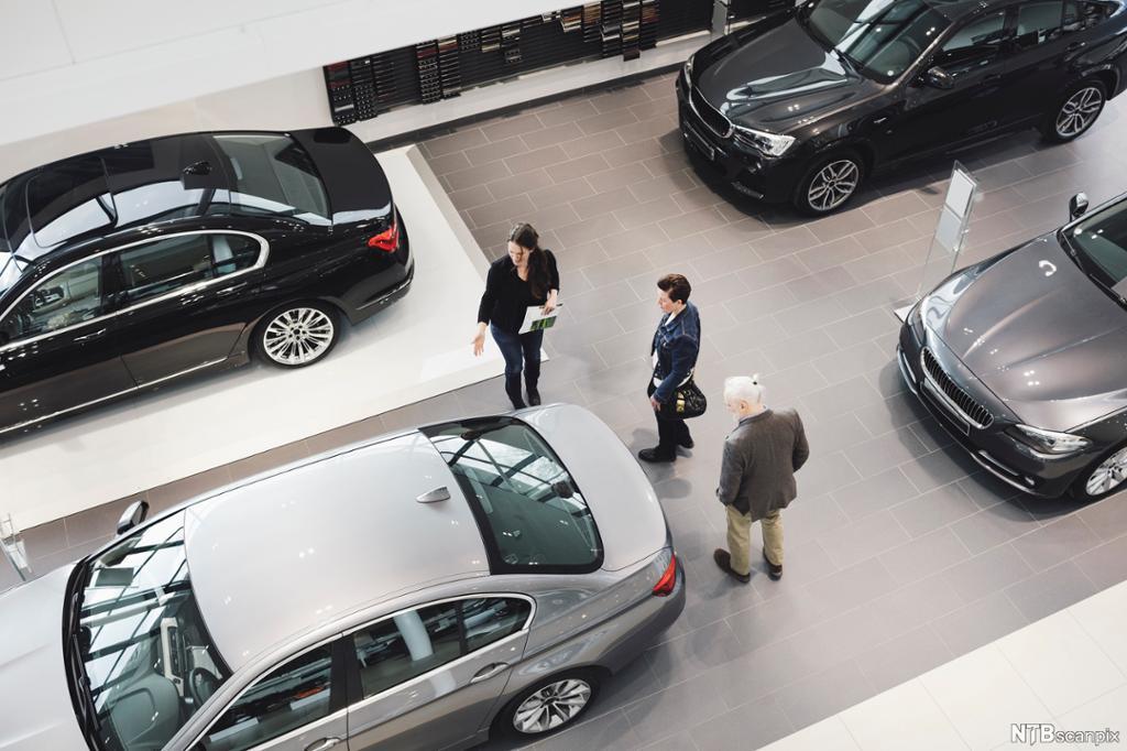 Flere personer ser på flotte biler i en bilutstilling. Foto.