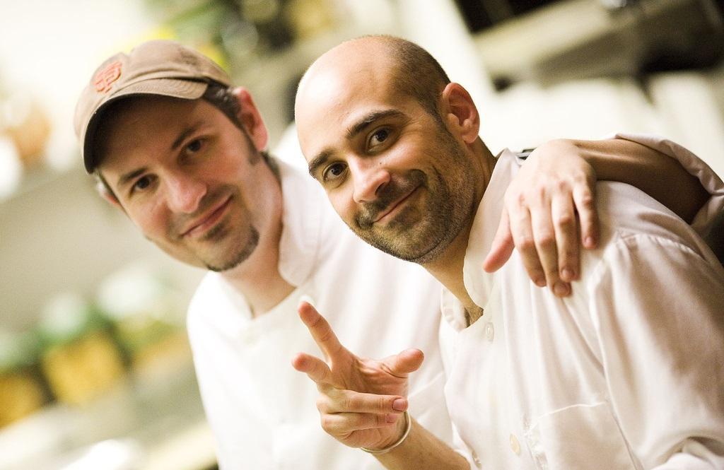 To glade kokker holder rundt hverandre på et kjøkken. Foto.