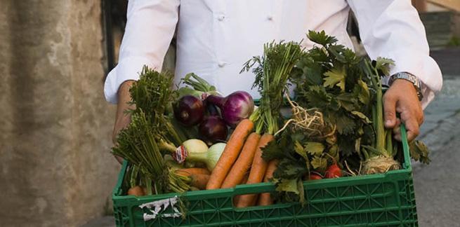 En kokk holder en kasse med grønnsaker. Foto.