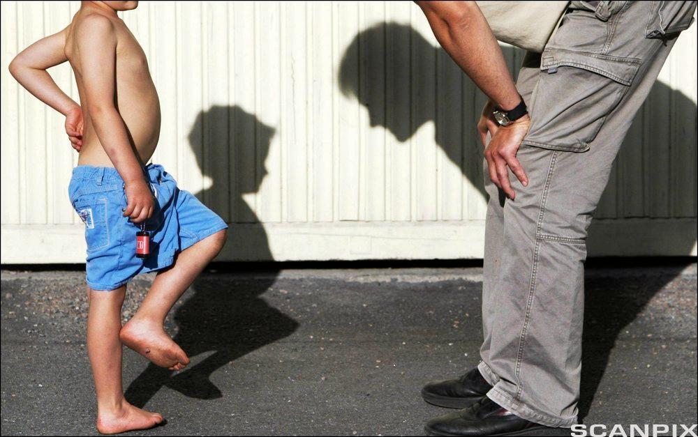 Far bøyer seg over og ser ned på sønnen. Foto.