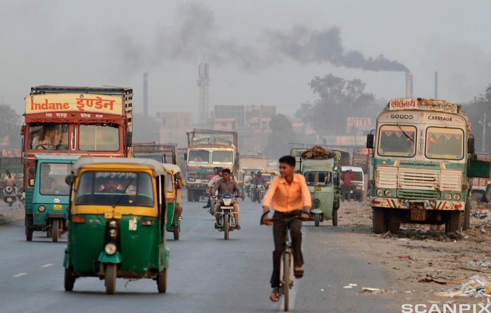 Gutt på sykkel i forurenset India. Foto.