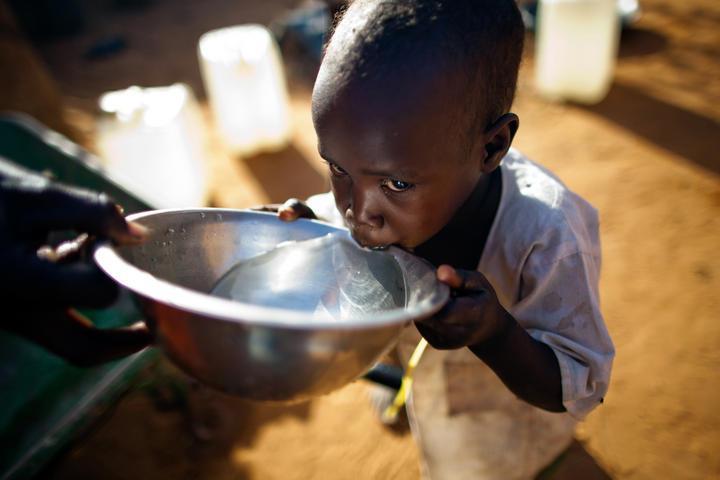 En liten gutt fra Darfur får rent vann å drikke. Foto.