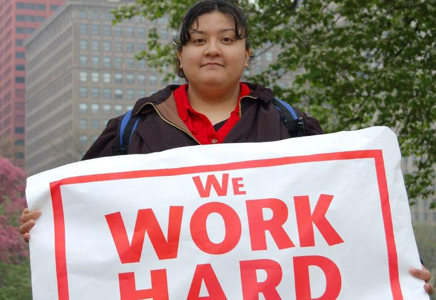 Woman holding poster saying We Work Hard. Foto.